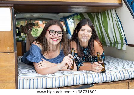 Summer holidays road trip vacation travel and people concept - smiling young hippie women in car