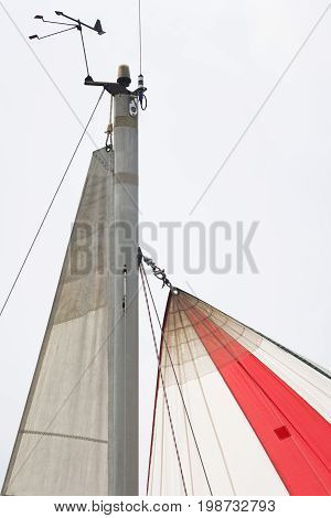 Yacht mast top with a cloudy sky as background