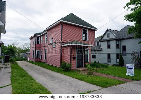 CADILLAC, MICHIGAN / UNITED STATES - MAY 31, 2017: An historic pink home is for sale in Cadillac's Courthouse Hill Historic District.