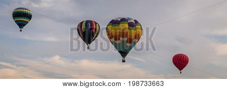 Colorful array of hot air balloons float through the sky at dusk for banner