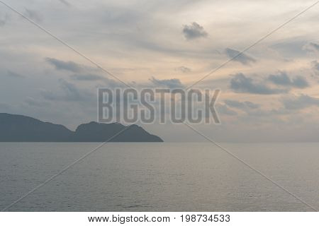 Morning sea and distant mountain land (a peninsula cape) on horizon in Prachuap Khiri Khan, Thailand. Early morning on the Gulf of Thailand