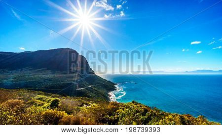 Low winter sun casting its rays over Smitswinkel Bay on the Cape Peninsula in the Western Cape province of South Africa under blue sky