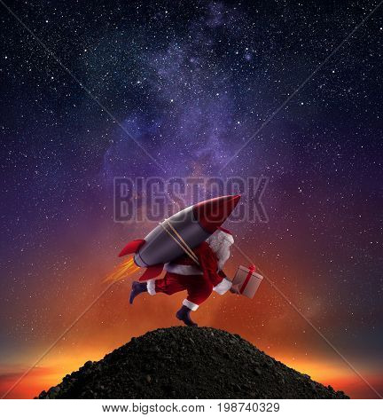 Santa Claus with gift box ready to fly with a rocket in the sky