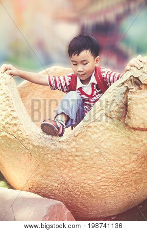 Happy asian child playing on playground. Handsome boy climbing simulation dinosaur egg. Concept about outdoor play for children on summer day. Travel on vacation. Vintage effect tone.