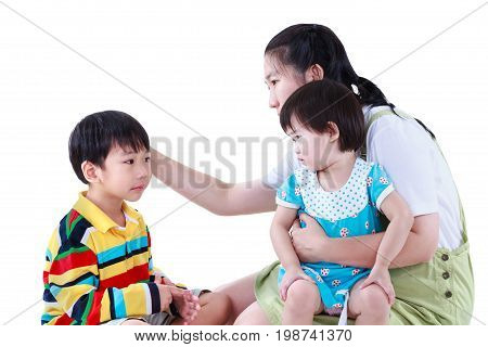 Asian mother with two children cute daughter sitting on lap. Son feel bad and sadden mom comforting. Great parenting image. Problems in the family. Isolated on white background. Studio shot.
