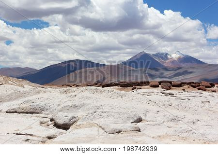 Colorful landscape with volcanic mountain snow peak under cloudy sky. Salt flats red rocks and volcanic mountains of San Pedro de Atacama Chile South America.