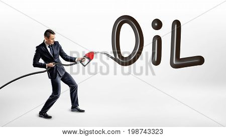 A businessman holds a gas nozzle and writes a large word Oil on white background. Oil and gas industry. Commodity trading. Procurement issues.