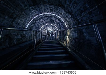 The flight of stairs - people are going up the steps - their silhouettes. Arched ceiling - a long narrow corridor, the descent into the salt mine. Salt mine - Solina Turda, Romania.
