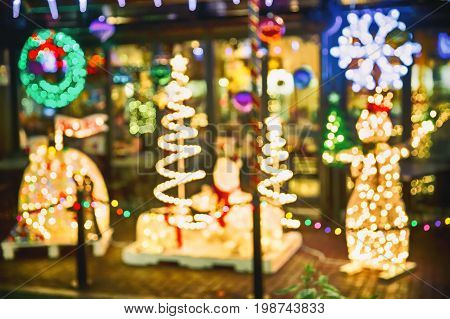 Christmas blurred background outdoors. Shop windows, street Christmas decorations and Christmas lights