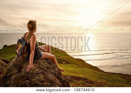 traveller with backpack enjoying sunset listening to music on peak of mountain. Mountains and sea landscape travel to Asia happiness emotion summer holiday concept