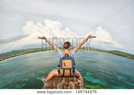 joyful woman traveler with backpack enjoying at the coast view with raised hands. Mountains and sea landscape travel alone to Asia happiness emotion summer holiday concept.