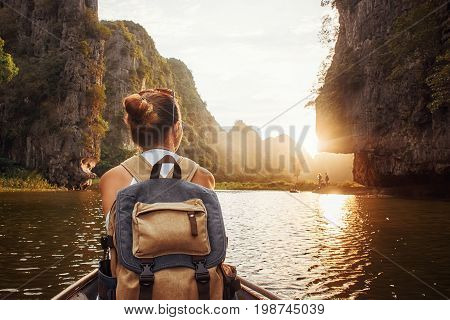 Woman with backpack swims on boat among karst mountains to meet her friends. Tam Coc North of Vietnam. Travel and active lifestyle summer holiday concept.