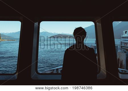 Man Looking Through Window On Ocean And Mountains