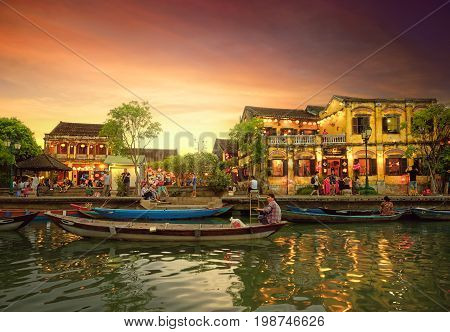 Hoi An Vietnam - May 8 2017: Street view with traditional boats on a background of ancient town in Hoi An Vietnam.