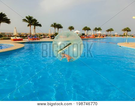 Sharm El Sheikh, Egypt - April 09, 2017: Little girl in an inflatable balloon, having fun on the water at Sharm El Sheikh, Egypt - April 09, 2017. The ball in the water - fascinating summer attractions for children. Water zorbing.