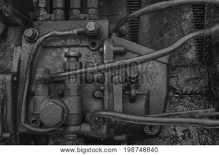 Old dirty diesel tractor engine with soot and oil. Black and white photo.