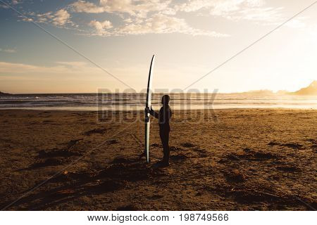 Man With Surf Walking On The The Beach With Forest Behind While Sunset