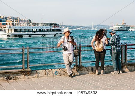 Istanbul, June 15, 2017: Elderly photographer and two young people on the pier in Istanbul, Turkey. In the background is the Bosphorus.