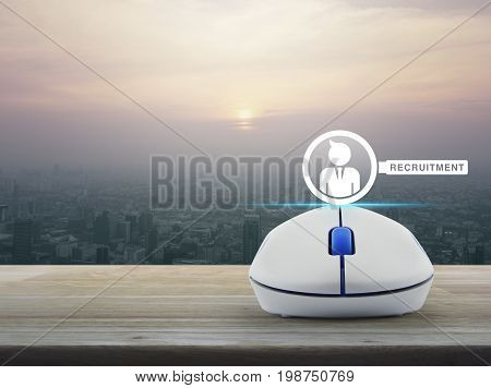 Businessman and magnifying glass icon with wireless computer mouse on wooden table over modern city tower at sunset vintage style Recruitment online concept