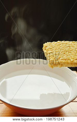 instant noodles dropping to hot water with smoked on bowl