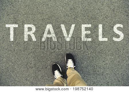 Word travels written on an asphalt road. Top view of the legs and shoes. POV