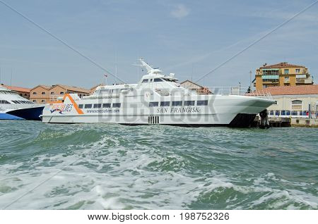 VENICE ITALY - JUNE 10 2017: view of the catamaran ferry San Frangisk part of the Venezia Lines fleet which transports passengers across the Adriatic between Venice and Croatia. Giudecca canal on a sunny summer afternoon.