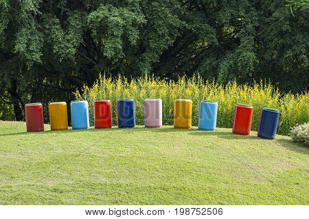 Decorate multi color concrete pipe stand on grass in park. Group of yellow flowers bush on mound green grass.