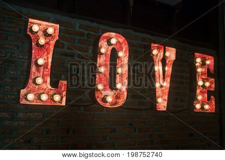 LOVE bulb sign decorated on brick wall stock photo