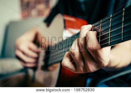 young musician playing acoustic guitar live music background