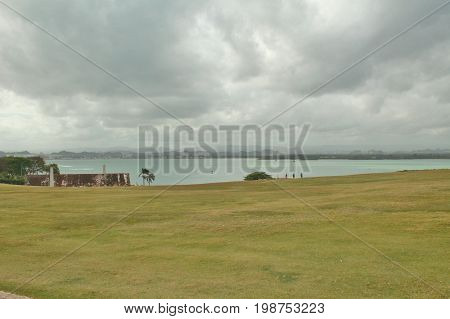 Dark cloudy skys aver the ocean and a grassy field foreground