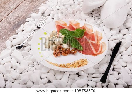 A white plate with prosciutto, blue cheese on white stones and on a wooden background. A composition of hamon, walnuts, basil and sauce on a plate. Romantic dinner at the restaurant.