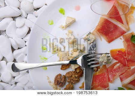 A view from above a white plate with remains of delicious food on a white stones background. The prosciutto or ham, walnuts, and cheese on a plate. Left-over food.