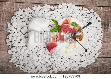 A top view of a white plate with remains of delicious food on a white stones background. The prosciutto, walnuts, and blue cheese on a plate. The inverted glass of wine near the dish. Left-over food.