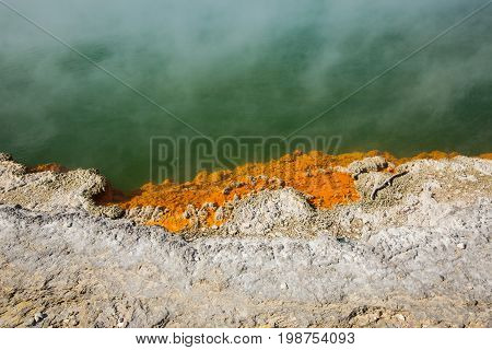 A picture of the edge of a hot spring Champagne Pool with smoke rising at Wai-O-Tapu Thermal Wonderland.