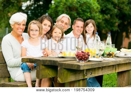 a big family are having a picnic in the garden