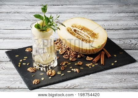 A highball glass full of alcoholic cocktail with a piece of carved melon on a gray wooden background. Sour, cold and alcoholic mojito with cut juicy melon, crushed walnuts, and cinnamon. Copy space.
