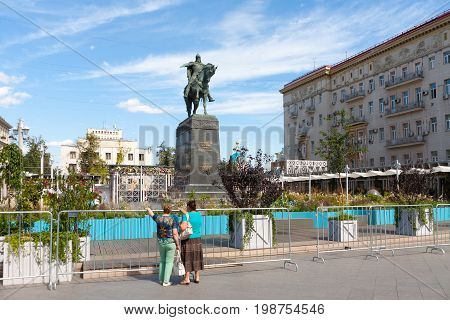 MOSCOW - AUGUST 7: Two women Yuri Dolgoruky monument and flower beds in Tverskaya Square on August 7 2017 in Moscow. Flower beds were installed during