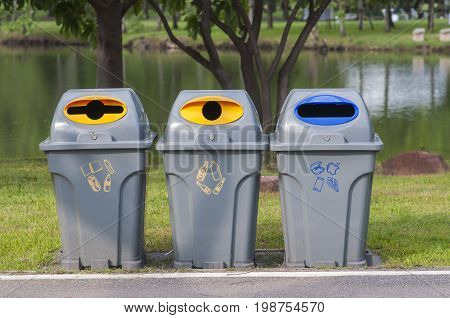 Color trash containers for seperate gabage. Trash bin along the way in park. Gabage seperate bin in park.