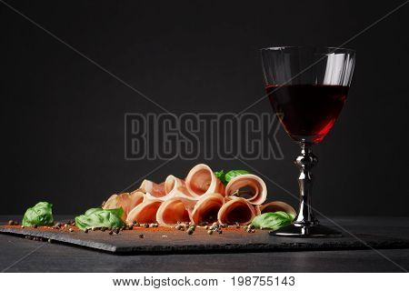 Beautifully sliced prosciutto and a glass of red wine on a black background. Appetizing traditional italian wine with meaty restaurant snacks. Delicatessen, luxury, celebration concept. Copy space.