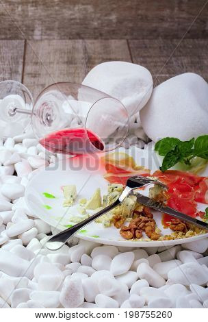 A beautiful composition of a delicatessen plate and a wineglass on white stones. A ceramic round plate with delicious snacks and a glass of semisweet red wine on a wooden background. Copy space.