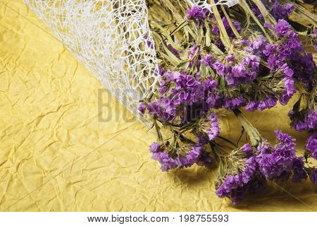 A view from above on a bright beautiful purple flowers on a yellow fabric background. Close-up picture of a natural bouquet of dried flowers. Floral herbarium. Nature concept. Copy space.