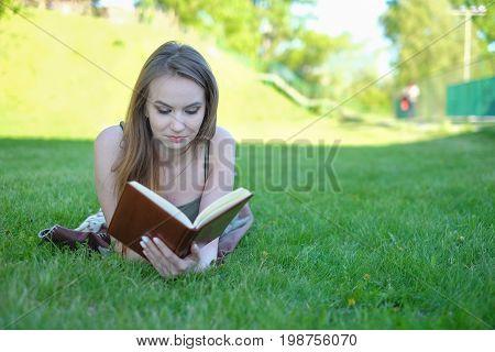 beautiful young woman reading book at park