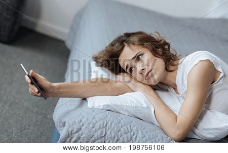 Where is he. Cheerless tired unhappy woman lying on the bed and looking at her smartphone screen while waiting for a call