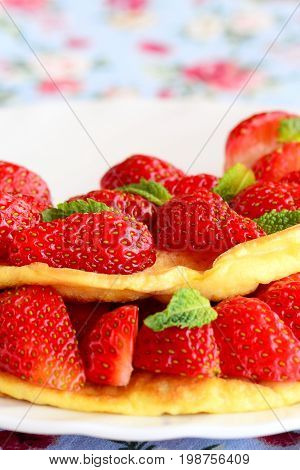 Sweet omelette stuffed with fresh strawberries on a white plate. Tasty and fluffy egg omelette idea. Breakfast recipe. Vertical photo. Closeup