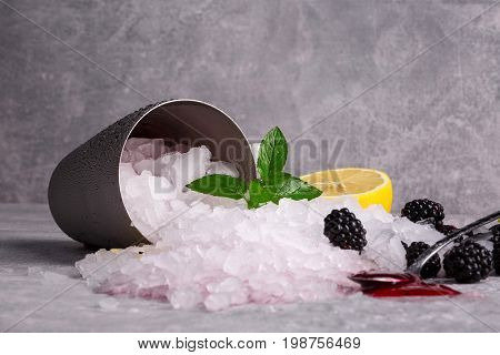 A metal bucket full of crushed ice on a gray table background. A long spoon with sweet berry jam and fresh, cold blackberries. Ice with peppermint and a cut lemon. Refreshing summer ingredients.