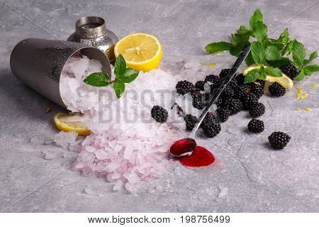 A gray metal bucket full of crushed ice on a light table background. A long spoon with sweet berry jam and fresh, cold blackberries. Ice with peppermint and a cut lemon. Refreshing summer ingredients.