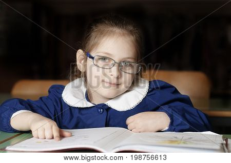 Little 6 years old girl first-grader with glasses