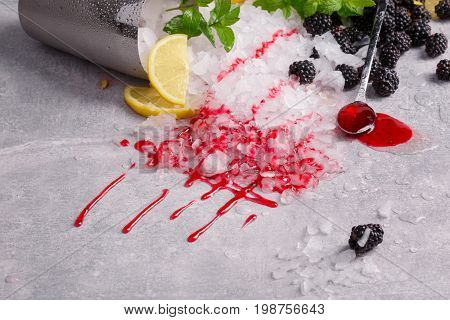 Metal bucket full of crushed ice on a gray stone table background. A long spoon with sweet berry jam and fresh, cold blackberries. Ice with mint leaves and a cut lemon. Refreshing summer ingredients.