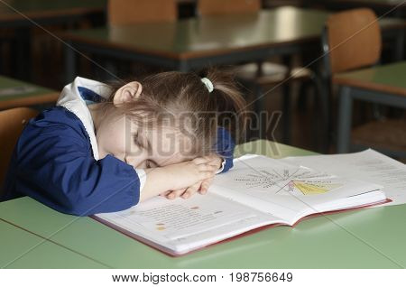 Tired italian elementary school girl first-grader sleeping on school desk. Educational and school concept