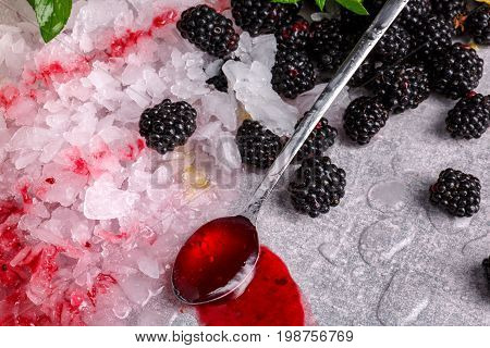 Close-up of crushed ice on a gray stone background. Crystal shards with a few ripe blackberries, dessert spoon and berry syrup. Organic ingredients for summer beverages. Tasty alcoholic cocktails.